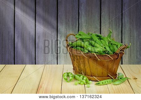 Basket of green peas in pods on a wooden table in the barn. Rural life. Agriculture. Rays of light on the pod. Summer.