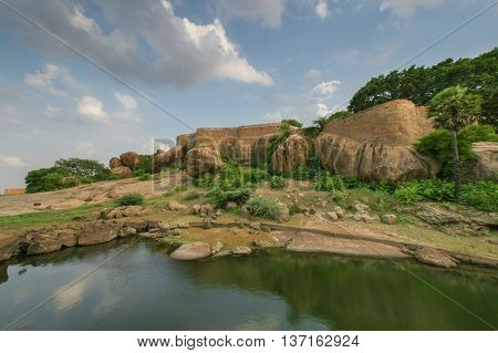 Chettinad India - October 16 2013: View from outside the Thirumayam fort on the fortifications. Boulders pond and trees in foreground under wide sky.