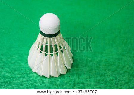 White badminton shuttlecock on a green court.