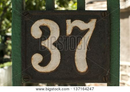 Old retro weathered cast iron plate with number 37