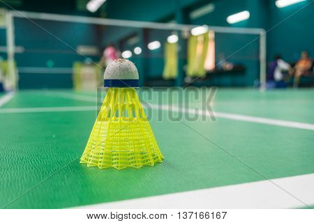 Yellow plastic badminton shuttlecock on a green floor with blurred players in badminton court.