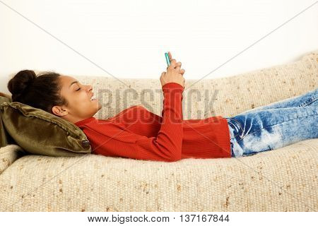 Beautiful Woman Lying On Couch With Smart Phone