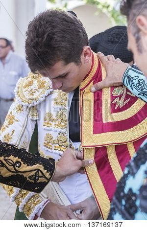Linares SPAIN - August 29 2014: Spainish bullfighter Daniel Luque putting itself the walk cape in the alley before going out to bullfight typical and very ancient tradition in Linares Jaen province Spain