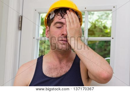 Young handsome construction worker in tank top and yellow hat