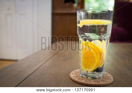 Fresh cold glass of water with juicy sliced lemon