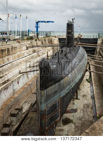 shipyard in the port with old rusty submarine under repair