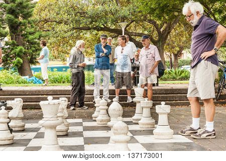 Sydney Australia - January 29, 2011; Group of men looking on in park in quiet contemplation while an outdoor game of chess is being played