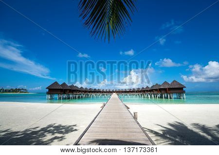 Troprical beach with water bungalows at Maldives