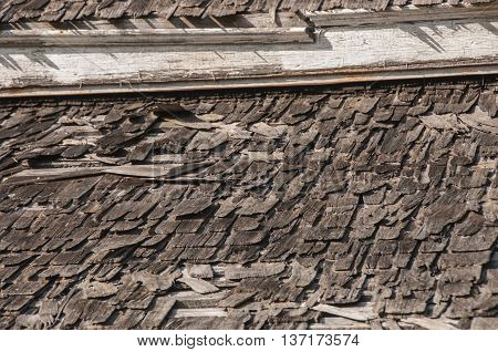 A broken on wood shingle roof on an old house.