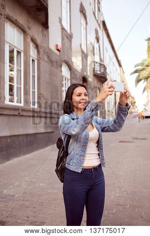 Pretty Young Girl In Narrow Street With Cell Phone