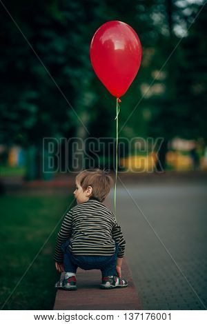 photo of little funny boy with red balloon