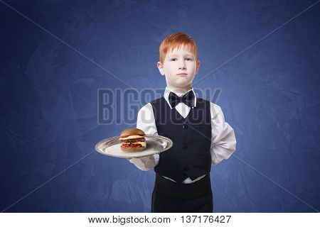Little waiter stands with tray serving hamburger. Redhead child boy in suit plays restaurant servant, gives burger at blue background