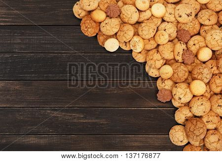Cookies background. Sweet chocolate chips biscuits heap at brown rustic wood background with copy space. Oatmeal, chocolated drops and other sweets. Fattening dessert for tea on wooden table top view