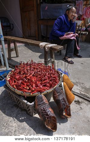 Zhaoxing Dong Village Guizhou Province China - April 8 2010: Outdoor trade on rural street dried chili is in a large basin next drying shoes and socks.