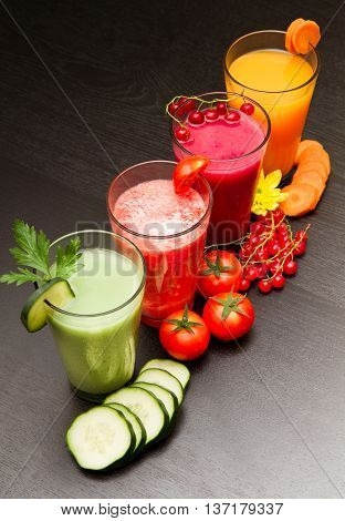 colored vegetable and fruit juice on black wood