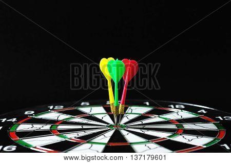 Three darts on bullseye with black background