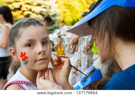 VOLGOGRAD RUSSIA - JUNE 26 2010: Artist paints mask on a girl's face on a children's holiday in the park in Volgograd