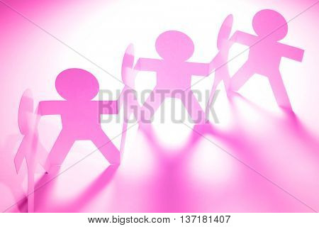 Pink paper doll people holding hands