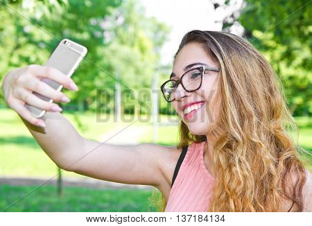 Outdoor portrait of beautiful girl taking a selfie with mobile phone