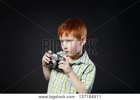 Little cute boy take photo with old vintage film camera at black background. Small redhead child photographer makes photograph.