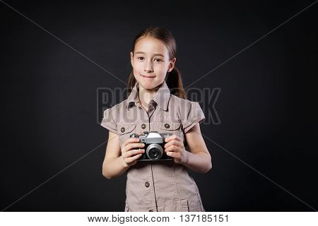 Little cute girl pose with old vintage film camera at black background. Small child photographer happy and smiling, studio portrait