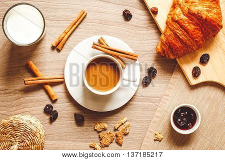 breakfast at home on wooden table with cup of milk coffee, croissants, macaroon top view