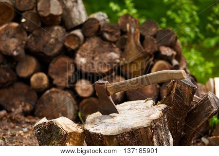 Old ax on a log and firewood in the background