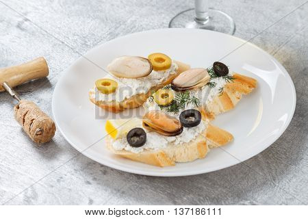 Tasty various italian sandwiches with seafood against rustic wooden background. Crostini with cheese mussels and olives on white plate and wine horizontal view