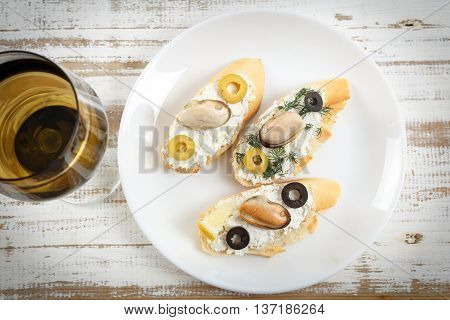 Tasty various italian sandwiches with seafood against rustic wooden background. Crostini with cheese mussels and olives on white plate glass of wine horizontal top view
