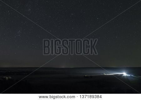Starry landscape. Summer night sky high above the plain. Single distant car lights at night meadow with clear starry sky.