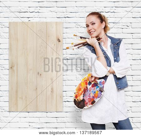 Happy artist. Woman with art tools. Female painter with brushes and palette. Empty wooden desk at white brick wall with copy space. Art classes for adults, education concept.