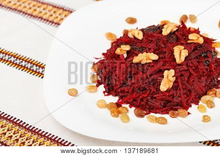 Grated beet salad with prunes raisins and walnut served on a white plate and home tablecloth. low aperture shot selective focus