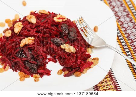 Tasting sweet salad with beets prunes and walnuts. Fork on the plate. Low aperture shot focus on front part of the shot