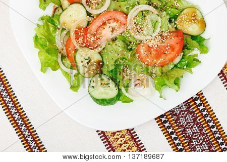Fresh salad with sliced tomato cucumber onion lettuce seasoned with soy sauce dry spices and sesame. Top view