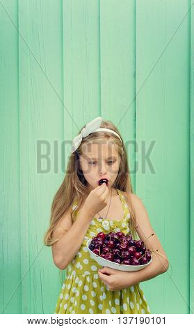 Beautiful blond girl on a background of turquoise wall holding a plate with cherry. Space for text
