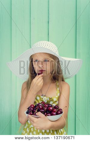 Beautiful blond girl on a background of turquoise wall in the white hat holding plate with cherry. Space for text
