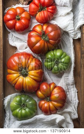 Colorful Heirloom tomatoes over white textile in rustic wooden tray, top view, vertical composition