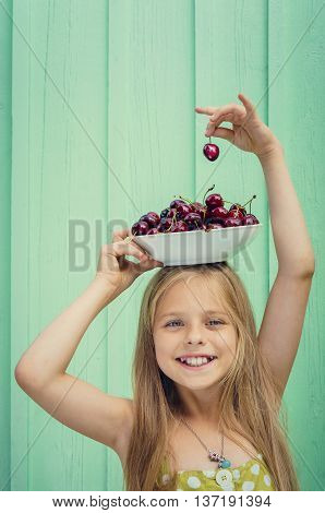 Beautiful blond girl on a background of turquoise wall holding a plate with cherries on her head. Space for text