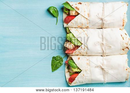 Healthy lunch snack. Three tortilla wraps with grilled chicken fillet and fresh vegetables over turquoise blue painted wooden background. Top view, copy space, horizontal composition