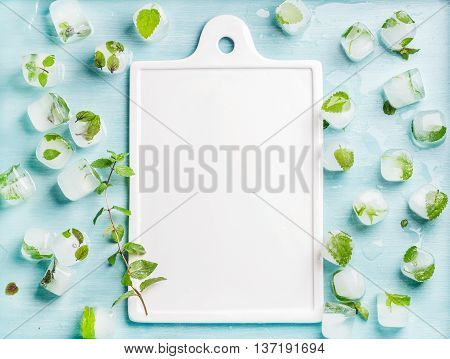 Ice cubes with frozen mint leaves inside on blue Turquoise background, white ceramic board with copy space in center, top view, horizontal composition