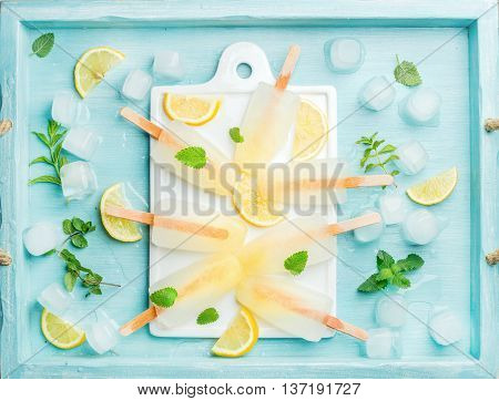 Ice lolly with lemon slices, fresh mint leaves and ice cubes on white ceramic board over blue Turquoise tray, top view, horizontal composition