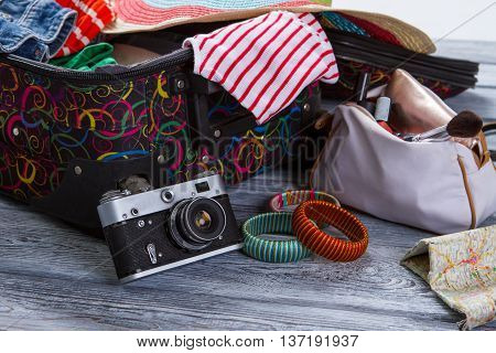 Camera near suitcase with clothes. Colorful striped bracelets. Vintage camera on gray shelf. Take some pictures during journey.