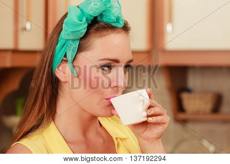 Pretty pin up girl with hairband bow drinking tea or coffee at home. Gorgeous young retro woman with hot beverage relaxing in kitchen.