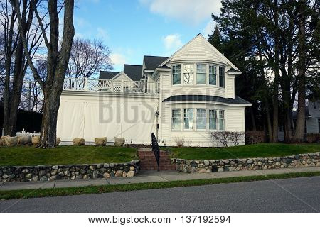 HARBOR SPRINGS, MICHIGAN / UNITED STATES - DECEMBER 25, 2015: An elegant white home on East Bluff Drive in Harbor Springs, with a view of Little Traverse Bay.