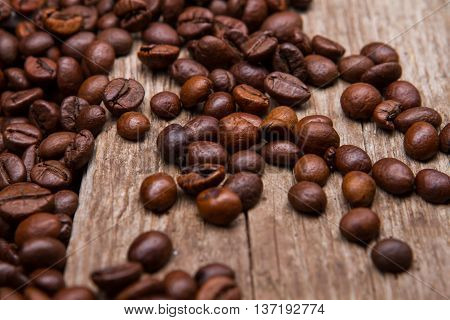 Coffee beans on wooden background. Brown coffee seeds. Old table with coffee grains. Imported coffee from India.