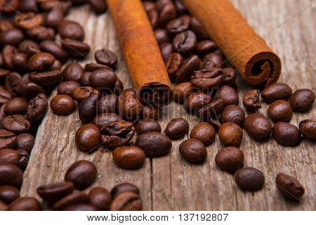 Coffee beans and cinnamon stick. Brown coffee grains and cinnamon. Spice for beverages. Aroma of robusta.