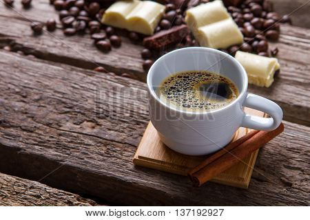 Coffee cup and cinnamon stick. Chocolate and coffee beans. Hot drink served with cinnamon. Simple morning dessert.