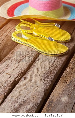 Flip flops near beach hat. Summer shoes on wooden surface. Travel to far islands. Sea air and bright sun.