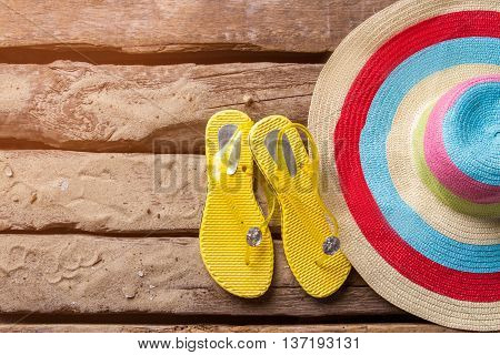 Striped beach hat and shoes. Flip flops of yellow color. Trip to a tropical place. Wood and sand.