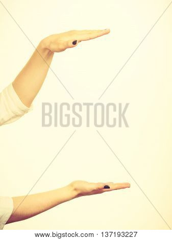 Woman showing presenting girl uses hands to indicate area of frame copy space for product graphic video or text. Presentation advertisement concept.